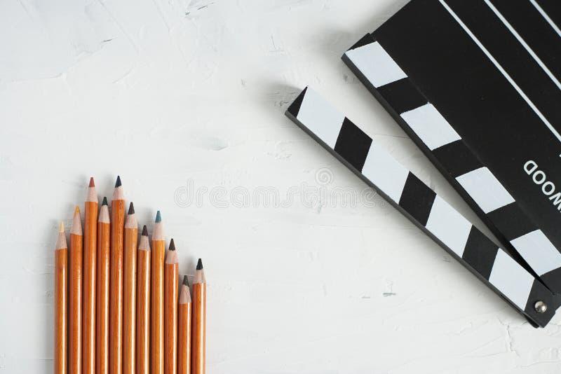 五颜六色的铅笔和黑电影拍板 免版税库存图片