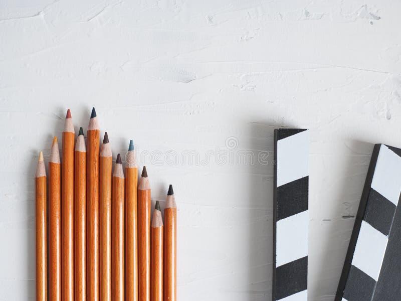 五颜六色的铅笔和黑电影拍板 免版税库存照片