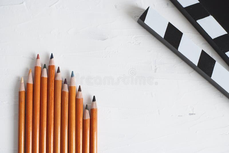 五颜六色的铅笔和黑电影拍板 图库摄影