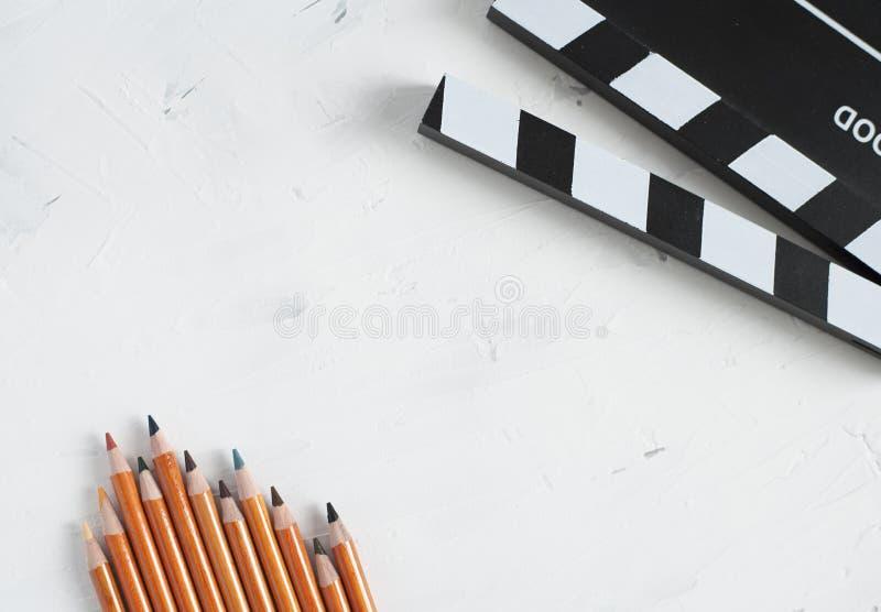 五颜六色的铅笔和黑电影拍板 库存图片