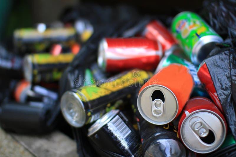 五颜六色的铝罐一起全部为回收金属废物帮助地球上的污染和是不伤环境的 库存照片
