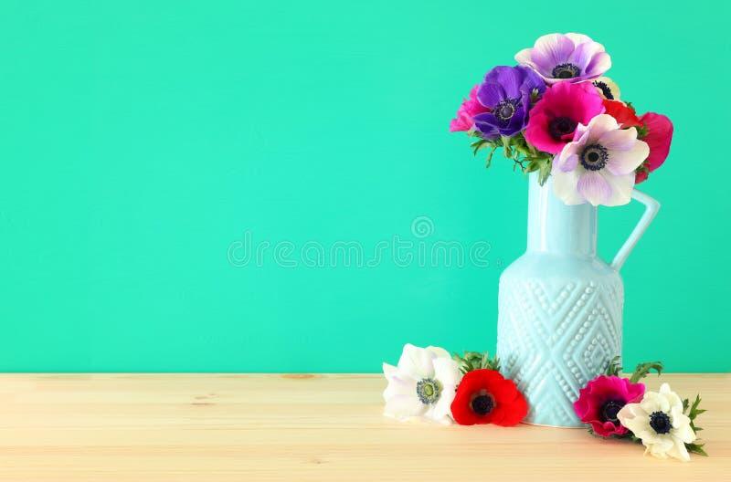 五颜六色的银莲花属春天花束在花瓶的在木桌 免版税库存照片