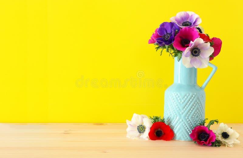 五颜六色的银莲花属春天花束在花瓶的在木桌 库存照片