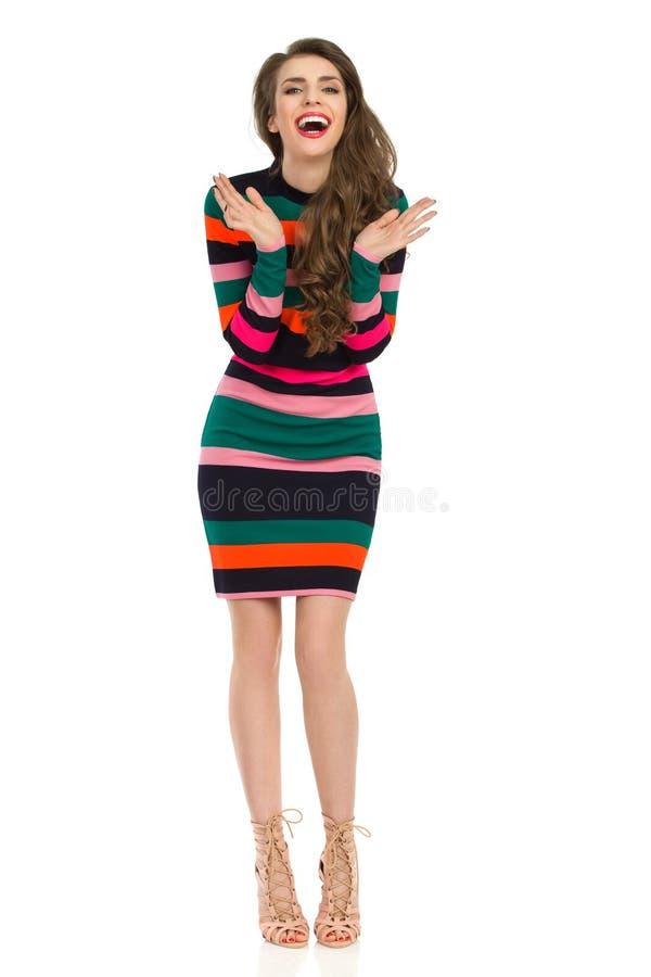 五颜六色的镶边套衫连超短裙的笑的激动的少妇 免版税库存图片