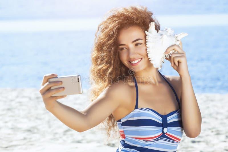 五颜六色的镶边泳装的一个年轻可爱的女孩由海拿着在海滩的大,白色壳并且做selfie 库存照片
