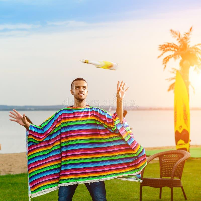 五颜六色的雨披的英俊的正面墨西哥侍酒者投掷  图库摄影