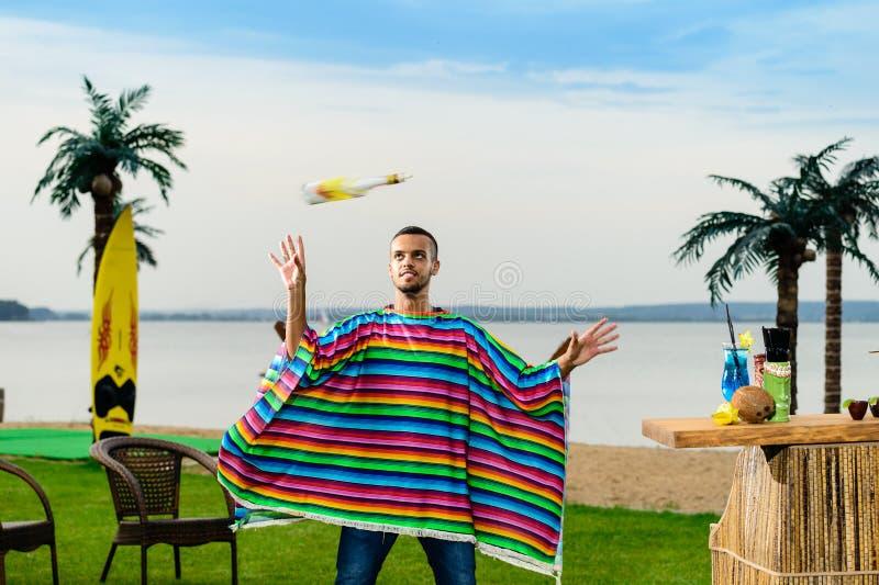 五颜六色的雨披的英俊的正面墨西哥侍酒者投掷  库存图片