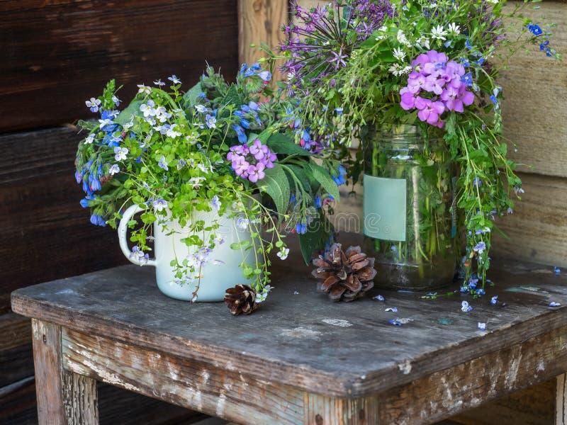 五颜六色的领域花花束  在一把老凳子的杉木锥体在土气门廊 免版税图库摄影