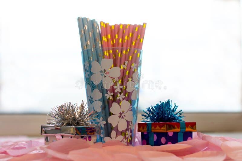 五颜六色的饮料管和一块美丽的蓝色玻璃与花饮料的 图库摄影