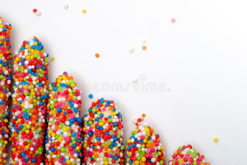 五颜六色的饼干棍子用白色空间背景涂搪瓷彩虹糖