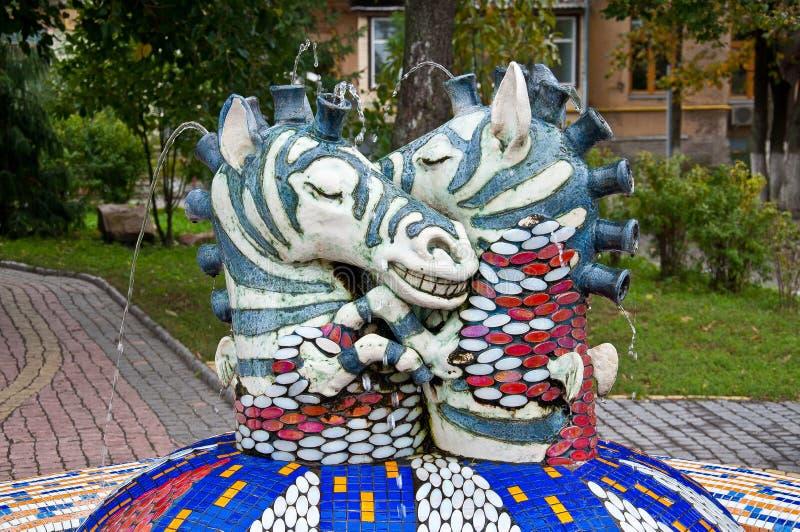 五颜六色的马赛克喷泉在有两个垂悬的斑马雕塑的基辅乌克兰 免版税库存照片