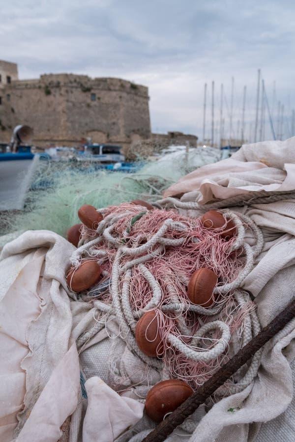 五颜六色的鱼网在港口在盖利博卢半岛,普利亚意大利 塑料鱼网可以污染和危险对海洋生活 免版税库存照片