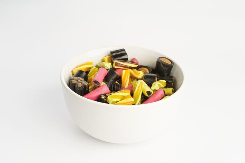 五颜六色的鲜美甜结束欧亚甘草糖果细节在白色背景的在碗 免版税库存照片