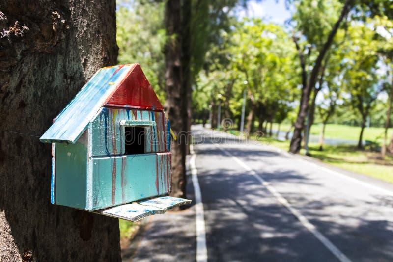 五颜六色的鸟和野生生物房子栓了对树在公园 库存照片