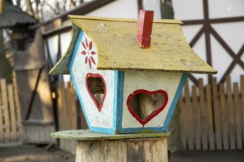 五颜六色的鸟饲养者 创造性的树上小屋用鸟的食物在冬天 库存图片