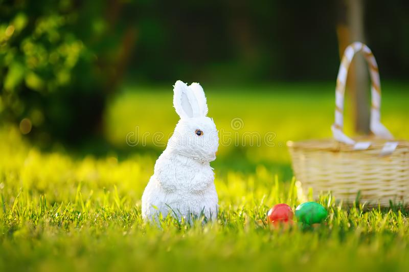 五颜六色的鸡蛋和逗人喜爱的白色玩具兔宝宝在鸡蛋期间在复活节寻找 免版税图库摄影