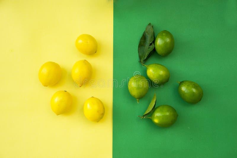 五颜六色的黄色和绿色柠檬,果子的概念想法顶视图在黄绿色淡色背景的,菜 免版税库存图片