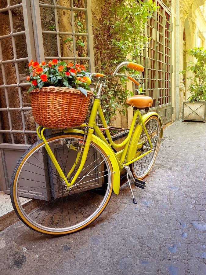 五颜六色的黄色自行车在老狭窄的街道上停放了在罗马, 图库摄影