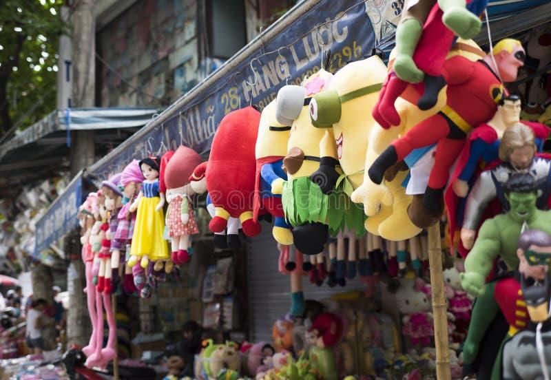 五颜六色的奴才和垂悬待售的超人木偶在河内处所街道的一条老街道 免版税库存图片