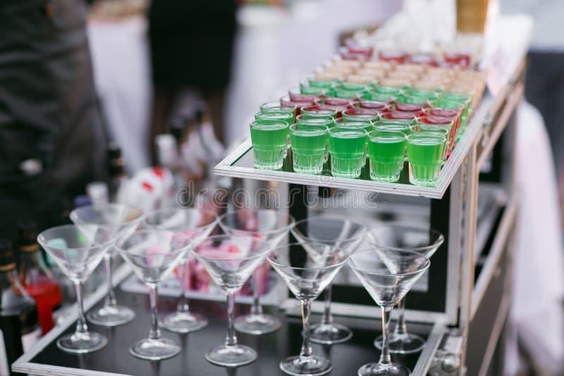 五颜六色的绿色红色和白色美丽的酒精甜射击者射击鸡尾酒新鲜的饮料品种在小玻璃的 免版税库存图片