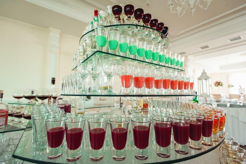 五颜六色的绿色黄色和红色酒精射击品种在站立在玻璃立场的行的小玻璃的 免版税库存图片