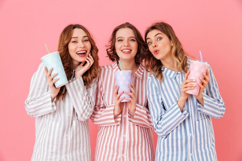 五颜六色的homewear的微笑的a三个迷人的女孩20s 库存照片