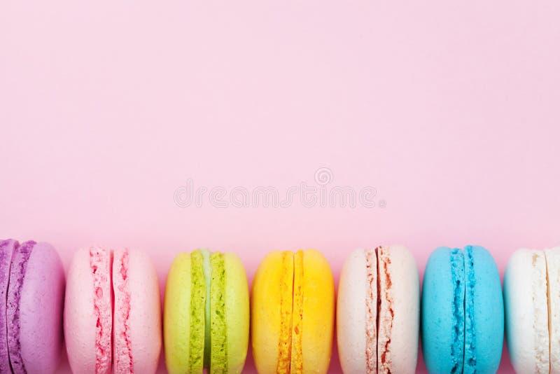 五颜六色的macaron或蛋白杏仁饼干在桃红色淡色背景顶视图 平的位置构成 库存图片