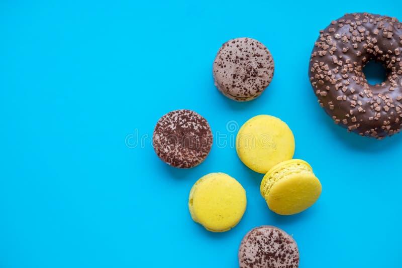 五颜六色的macarons结块,顶视图舱内甲板位置,在糖果蓝色背景的甜蛋白杏仁饼干 上面最小的概念样式,食物 免版税库存照片