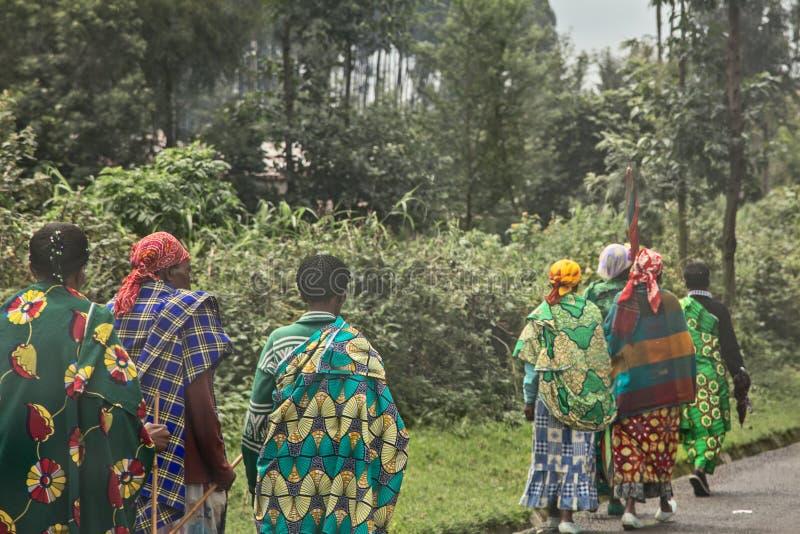 五颜六色的traditionals衣裳的农村卢旺达妇女走沿路,基加利,卢旺达的小组  图库摄影