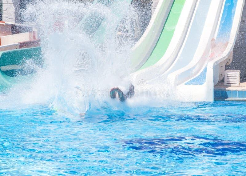 五颜六色的waterpark管、浪花幻灯片和水池在aquapark 水公园滑接近  库存照片