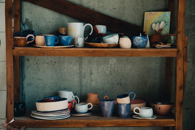 五颜六色,白色和蓝色陶瓷杯子和盘在瓦器商店架子  免版税图库摄影