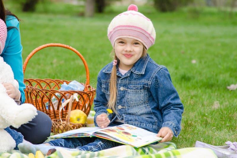 五年的女孩坐绿色草坪 库存照片