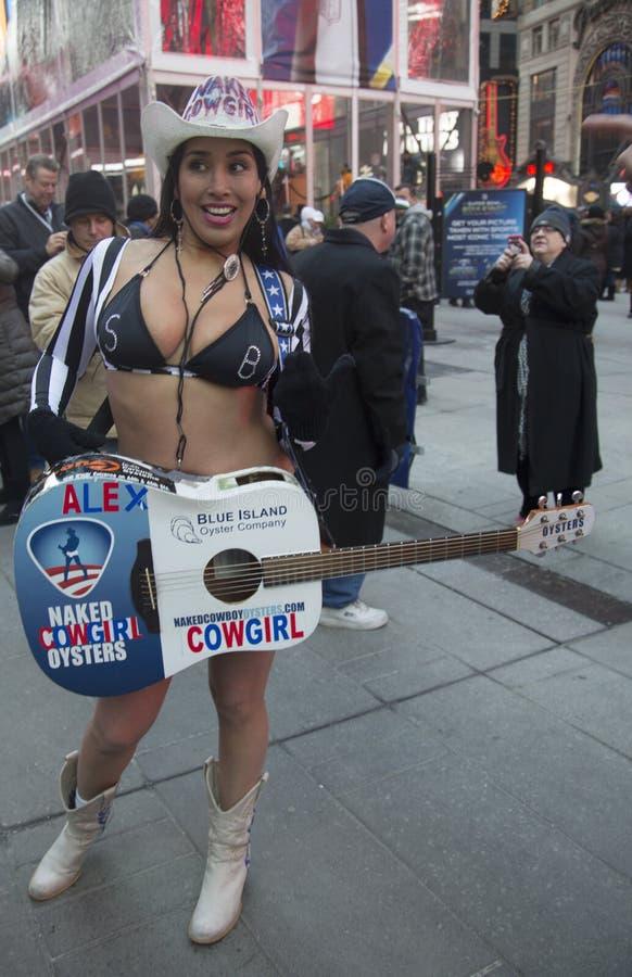 亚历克斯,赤裸女牛仔,招待人群在时代广场在超级杯XLVIII星期期间在曼哈顿 免版税库存照片