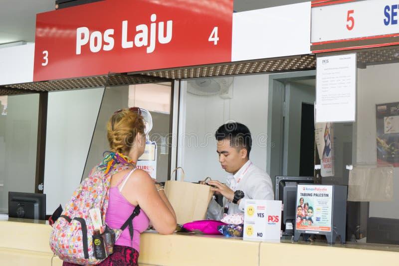 亚庇沙巴马来西亚- 2017年8月26日, :一个逆职员被协助的一个未认出的旅游夫人 Pos Laju Mala 免版税库存照片