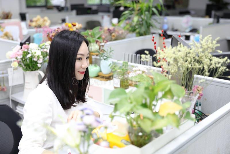 亚洲中国办公室夫人妇女女孩坐椅子在工作用途便携式计算机微笑穿戴企业职业衣服工作场所 库存图片