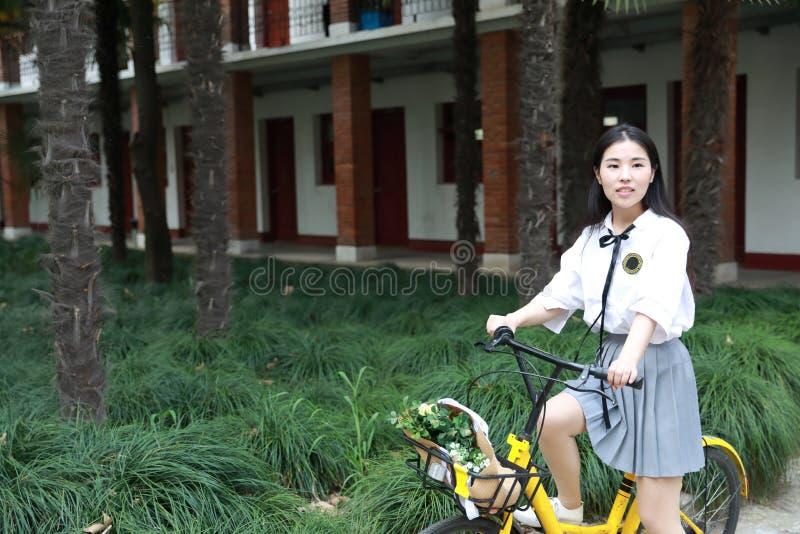 亚洲中国愉快的逗人喜爱的可爱的可爱的学生乘驾黄色在她的教室前分享了自行车在学校 库存图片