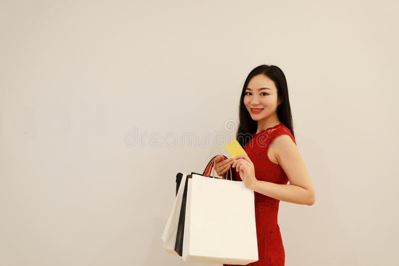 亚洲中国现代时髦的女人女孩购物卡片和袋子在购物中心白色在手边隔绝了背景 免版税库存照片
