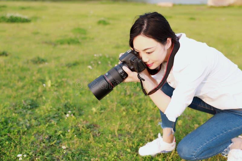 亚洲中国自然妇女摄影师看看的画象她的在春天公园森林周围的照相机屏幕由花 库存照片