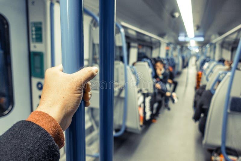 亚洲人手藏品扶手栏杆或杆特写镜头在火车里面在公交 库存图片