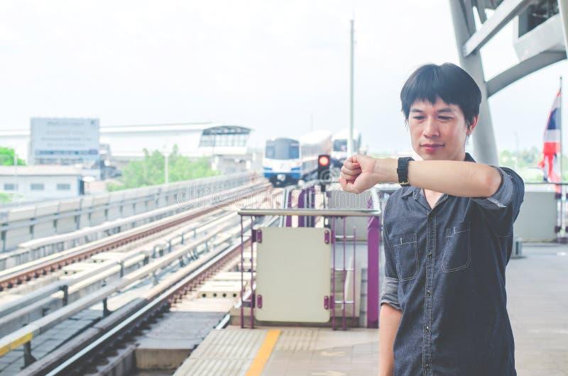 亚洲人立场看法和看他的手表,当等待某事或担心时间时 作为背景的行动火车 免版税库存照片