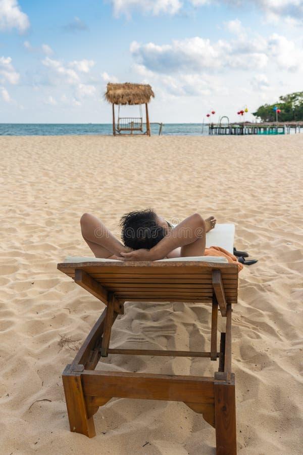 亚洲人sunbath垂直的照片和放松在海滩 免版税库存照片