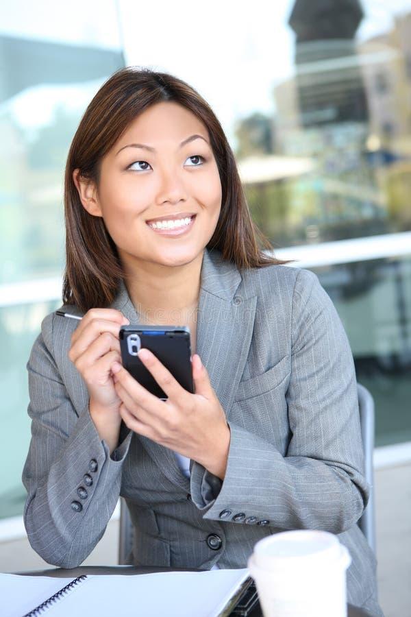 亚洲企业俏丽的texting的妇女 免版税库存图片