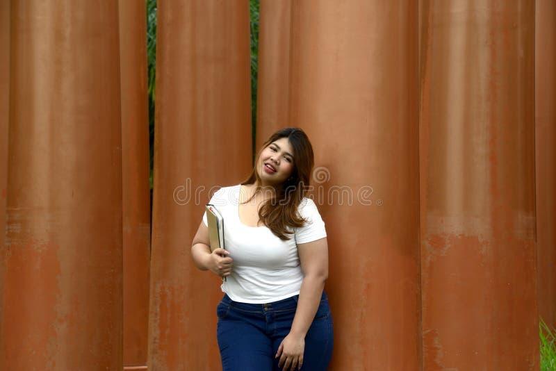 亚洲俏丽的兴高采烈的面孔肥胖妇女姿势身分画象和拿着一本小册子手中 免版税库存图片