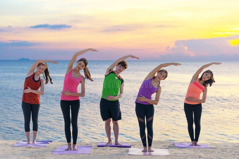 亚洲健康人生活方式小组行使重要在海滩思考和实践的瑜伽姿势和培训班 免版税库存图片