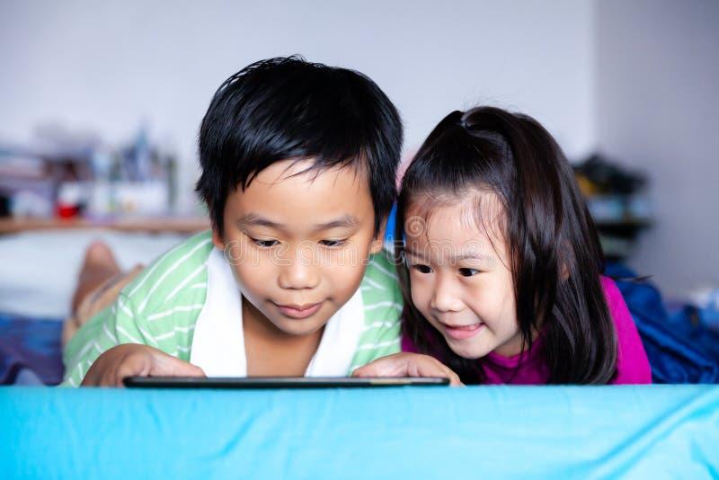 亚洲儿童观看录影和打在数字式片剂的比赛 库存图片