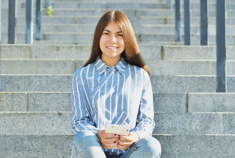 亚洲出现的少女,在牛仔裤打扮的学生和镶边衬衣,在她的手上拿着一种片剂并且坐 免版税库存照片