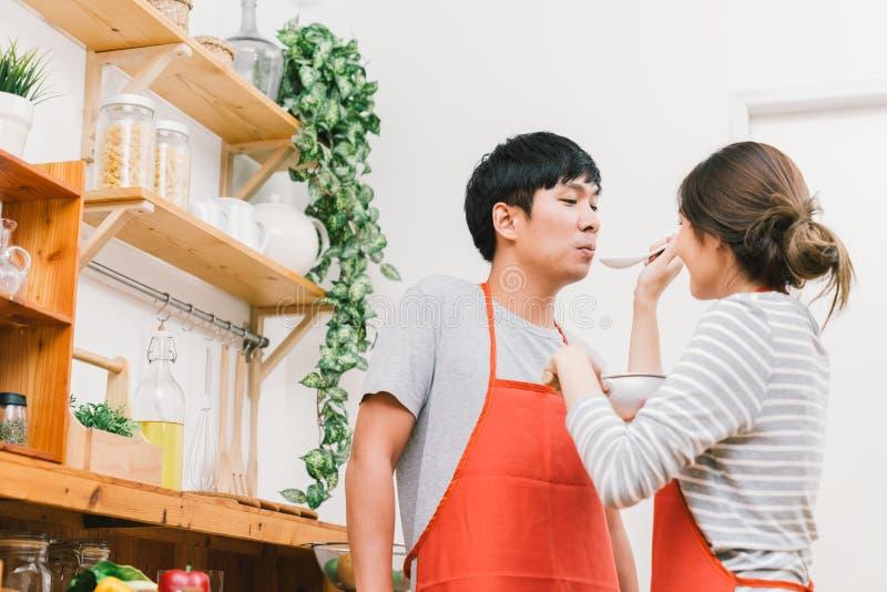 亚洲可爱的夫妇在家一起烹调厨房,品尝准备膳食的食物 女孩对使用匙子的男朋友的饲料汤 免版税库存图片