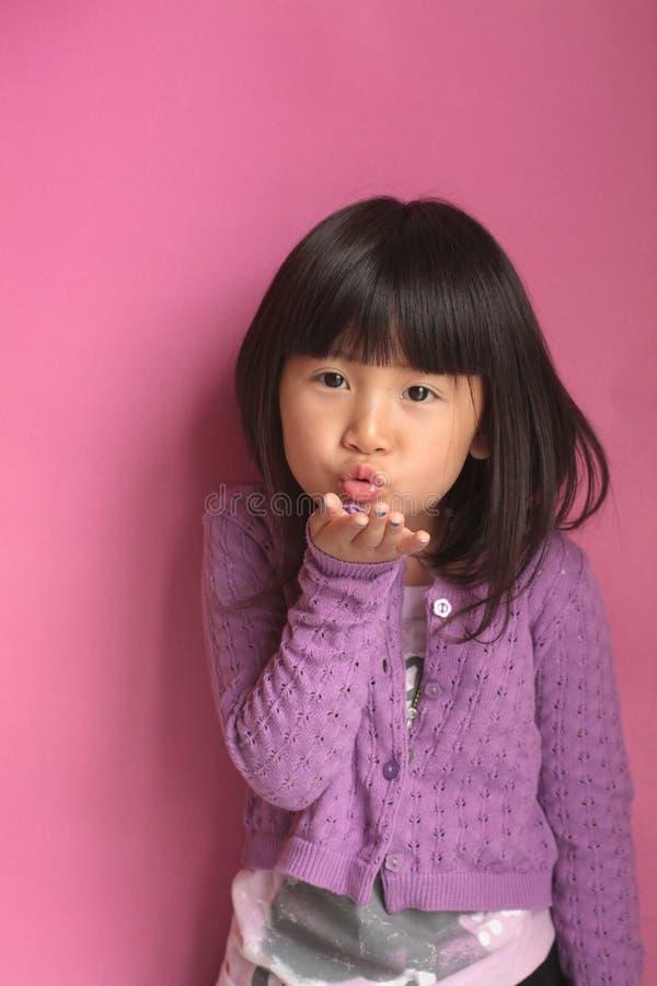 亚洲吹的女孩亲吻 库存照片