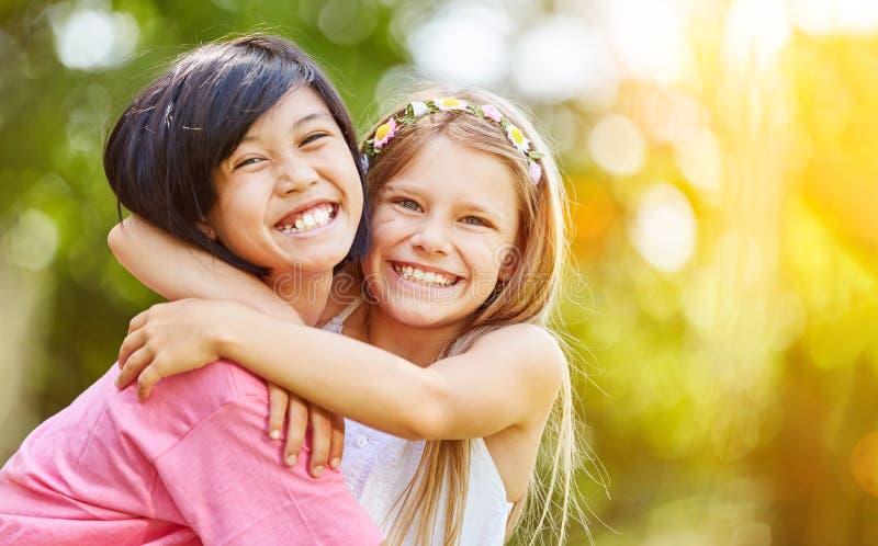 亚洲和白种人女孩拥抱 免版税图库摄影