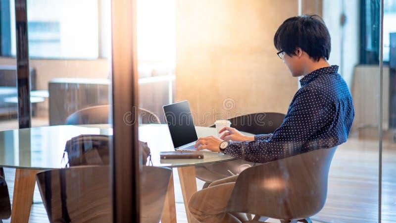 亚洲商人与膝上型计算机一起使用在会议室 库存照片